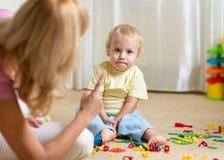 Mãe que censura sua criança na brincadeira em casa imagem de stock