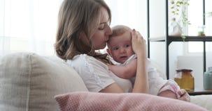 Mãe que consola sua filha do bebê no sofá em casa video estoque