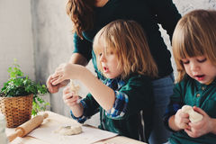 Mãe que cozinha com as crianças na cozinha Irmãos da criança que cozem junto e que jogam com pastelaria em casa Imagens de Stock Royalty Free