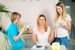 Mãe que dá a suas crianças o dinheiro de bolso fotografia de stock royalty free