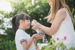 Mãe que dá um gatinho a sua filha foto de stock