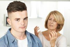 Mãe que discute com o filho adolescente em casa imagens de stock royalty free
