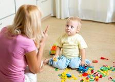 Mãe que discute sua criança na brincadeira em casa imagens de stock royalty free