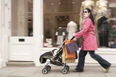 Mãe que empurra o carrinho de criança pela loja de roupa Foto de Stock