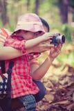 Mãe que ensina a filha asiática bonita que toma fotos outdoors fotografia de stock royalty free