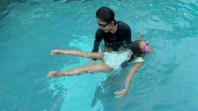 Mãe que ensina sua filha nadar