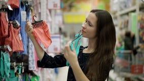 Mãe que escolhe a roupa para a posição do bebê perto de uma prateleira da roupa das crianças no supermercado, compra, alameda filme