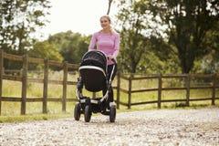 Mãe que exercita correndo enquanto empurrando o carrinho de bebê imagens de stock royalty free