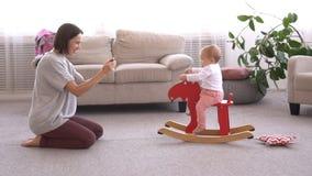 Mãe que fotografa o bebê que joga em cervos de balanço em casa vídeos de arquivo