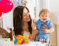 Mãe que guarda o bebê na festa de anos imagem de stock
