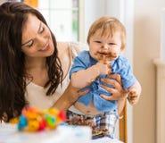 Mãe que guarda o bebê que come o bolo com crosta de gelo sobre imagens de stock