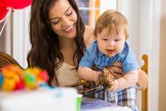 Mãe que guarda o bebê que come o queque imagens de stock