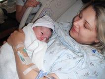 Mãe que guarda o bebê recém-nascido após a entrega fotos de stock