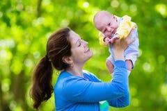 Mãe que guarda o bebê recém-nascido em um parque Fotos de Stock