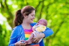 Mãe que guarda o bebê recém-nascido em um parque Fotos de Stock Royalty Free