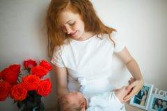Mãe que guarda sua criança em seus braços fotografia de stock royalty free