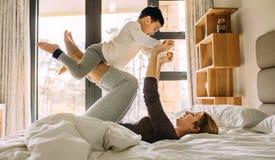 Mãe que joga com a criança na cama foto de stock royalty free