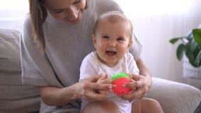Mãe que joga com o bebê bonito no sofá vídeos de arquivo