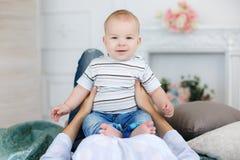 Mãe que joga com o bebê que encontra-se na cama Foto de Stock