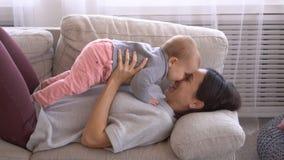 Mãe que joga com seu bebê infantil no sofá vídeos de arquivo