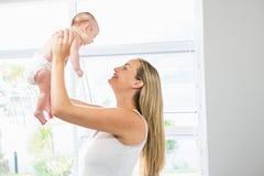 Mãe que joga com seu bebê na sala de visitas imagem de stock