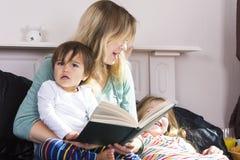 Mãe que lê às crianças na cama imagens de stock