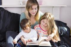 Mãe que lê às crianças na cama foto de stock