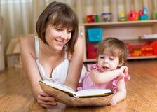 Mãe que lê um livro para caçoar imagem de stock royalty free