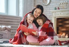 Mãe que lê um livro a suas filhas foto de stock royalty free