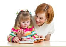 Mãe que lê uma criança do livro imagens de stock