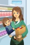 Mãe que leva seus sacos da filha e de mantimento Foto de Stock