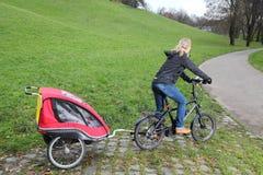 Mãe que monta uma E-bicicleta com reboque da criança Fotografia de Stock