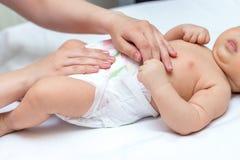 Mãe que muda um tecido do seu recém-nascido imagens de stock