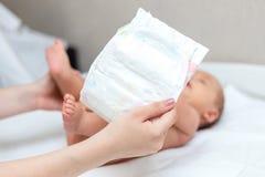 Mãe que muda um tecido do seu recém-nascido foto de stock royalty free