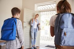 Mãe que obtém crianças prontas para sair da casa para a escola fotos de stock royalty free