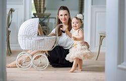 Mãe que olha seu bebê jogar o transporte Fotografia de Stock