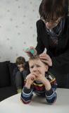 Mãe que procura piolhos na cabeça dos jovens foto de stock