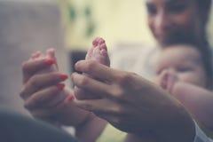 Mãe que realiza em seus pés do bebê das mãos fotos de stock