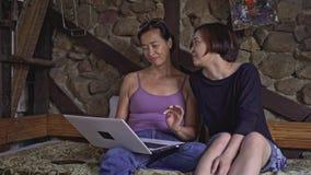 A mãe que senta-se com o portátil na cama, filha vem conversar vídeos de arquivo