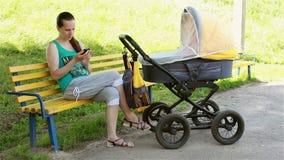A mãe que senta-se no parque rola o carrinho de criança e a vista do smartphone video estoque