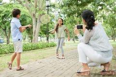 Mãe que toma a imagem das crianças que jogam o badminton fotos de stock