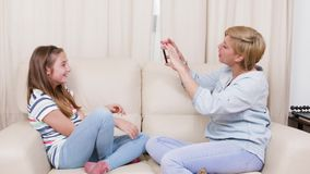Mãe que toma imagens de sua filha ao relaxar em um sofá video estoque