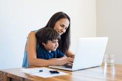 Mãe que trabalha em casa com filho imagens de stock