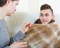 Mãe que trata o adolescente com o xarope em casa Imagens de Stock