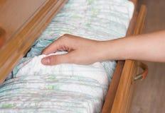 A mãe remove um tecido para sua criança da prateleira, close-up fotos de stock