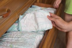 A mãe remove um tecido para sua criança da prateleira, close-up fotos de stock royalty free