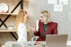 Mãe resoluto no revestimento vermelho que tem a conversação séria imagens de stock royalty free