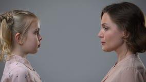 Mãe restrita que olha a filha assustado no fundo cinzento, educação da disciplina filme