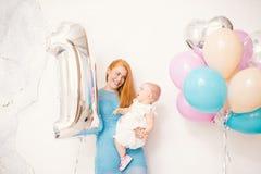 Mãe ruivo nova que guarda um bebê um ano em um vestido em um fundo branco em casa O conceito de um holida do ` s das crianças Foto de Stock Royalty Free