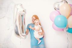 Mãe ruivo nova que guarda um bebê um ano em um vestido em um fundo branco em casa O conceito de um holida do ` s das crianças Fotos de Stock